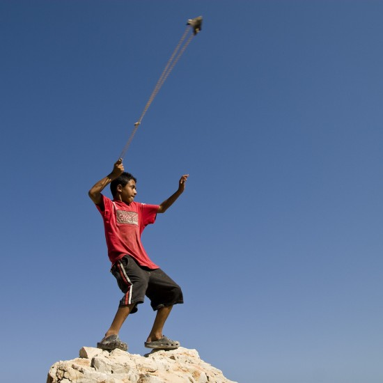 Young boy on rock with slingshot. David, not goliath